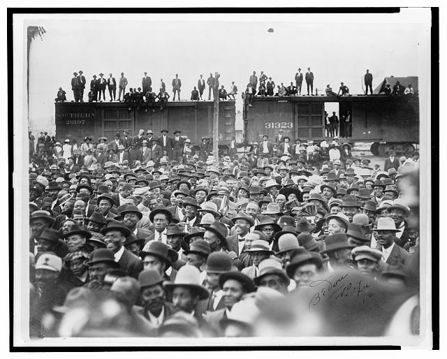 [Large crowd gathered to hear Booker T. Washington speak, with men standing on railroad box cars in the background, New Orleans, Louisiana]
