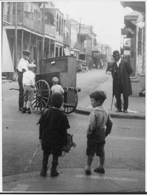 New Orleans La [Street scene showing 4 children and an African American man watching another African American man with a hurdy-gurdy