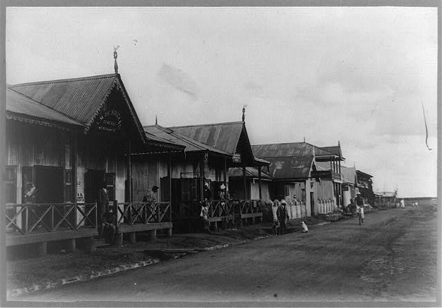 One story frame houses with wooden front porches line a dirt road with stone gutter. Planks provide access from roadway across the gutter to wooden front porches. People stand on the porches, a man rides a bicycle in the street, a dot sits in the street.